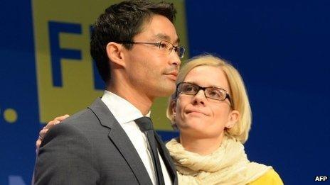 German free democratic party FDP party chairman Philipp Roesler (L) is comforted by his wife Wiebke
