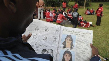 A man looks at a newspaper bearing funeral arrangements of victims of the Westgate mall terrorist attack in Nairobi, on 24 September 2013