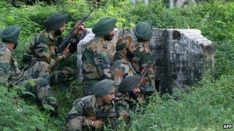 Indian army soldiers gather behind a wall during an attack by militants on an army camp at Mesar, Kashmir. Photo: 26 September 2013
