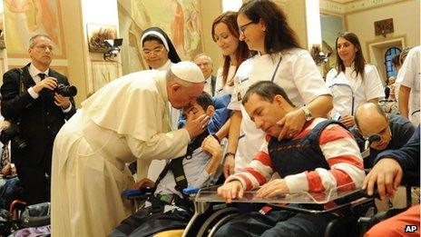 Pope Francis caresses a person during his visit at the Serafico Insitiute for disabled children, in Assisi, Italy, on 4 October 2013