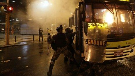Riot policemen try to extinguish a fire in a bus after demonstrators set fire to it during a protest in Rio de Janeiro on 7 October 2013.
