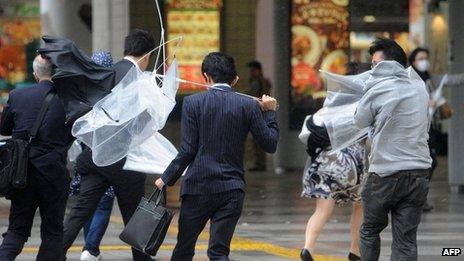 People walk against strong wind and rain in Tokyo on 16 October 2013