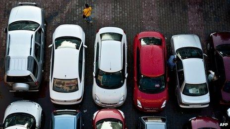 An Indian pedestrian walks past cars at a parking lot in New Delhi (file photo)