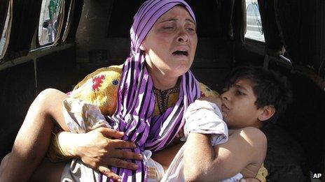 A Syrian mother carrying her injured son escapes into Lebanon (file photo)