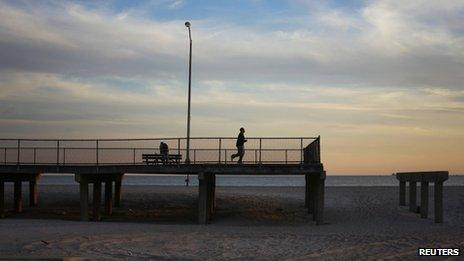 A jogger runs to the end of a boardwalk damaged by Hurricane Sandy in October 2012 in the borough of Queens in New York October 28, 2013