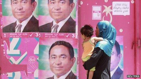 A Maldivian woman looks at posters of Maldivian presidential candidate Abdullah Yameen ahead of their presidential election in Male, 7 November 2013