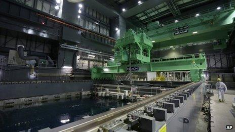A Tepco employee walks past a fuel handling machine on the spent fuel pool inside the building housing the Unit 4 reactor at the Fukushima Dai-ichi nuclear power plant on 7 November 2013