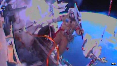 Image obtained from NASA TV showing cosmonaut Oleg Kotov exiting the International Space Station on 9 November 2013 with the Sochi 2014 Winter Olympic Games torch.