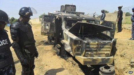 Police look down on a burned out army personal carrier following an attack by Boko Haram in Damaturu, Nigeria