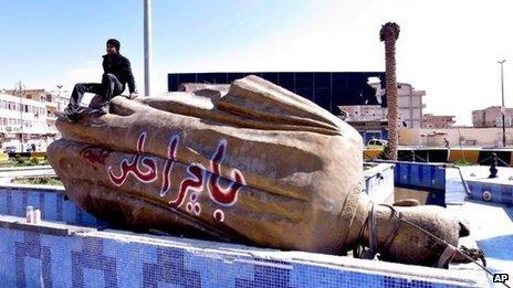 A man sits on a statue of President Hafez al-Assad in Raqqa