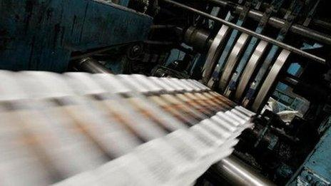 Newspapers roll off a printing press.