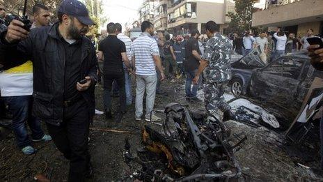 A security personnel officer looks back as he walks past a burnt motorcycle at the site of explosions near the Iranian embassy in Beirut