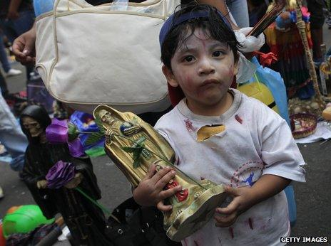 Child with statue of Santa Muerte