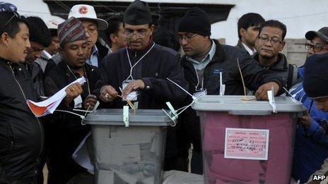 A Nepalese election worker seals a ballot box after poling closed in Kathmandu on 19 November 2013