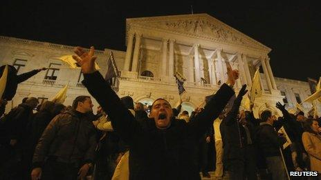 A demonstrator shouts after breaking through a line of policemen guarding the Portuguese parliament in Lisbon 21 November.