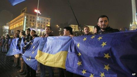 Activists wave Ukrainian and European Union flags during a night rally in support of Ukraine's integration with the European Union in Kiev