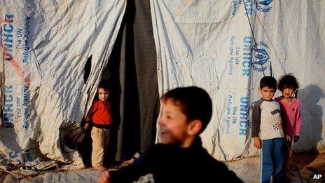 Syrian refugee children stand in front of their tents, at Zaatari Refugee Camp, in Mafraq, Jordan (5 Nov. 2013)