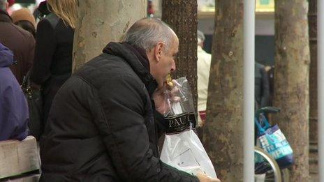 Man eating lunch on bench