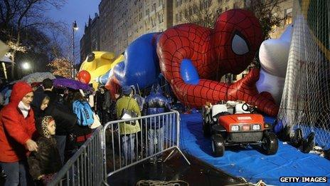 Sightseers photograph giant balloons the evening before the Macy's Thanksgiving Day Parade in New York City on 27 November 2013