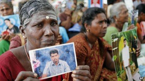 Sri Lankan ethnic Tamil women cry holding portraits of their missing relatives during a protest in Jaffna, Sri Lanka, Friday, Nov. 15, 2013