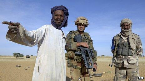 A French soldier and Malian interpreter talk with a nomad near the village of Bamba between Timbuktu and Gao, northern Mali, on October 30, 2013,