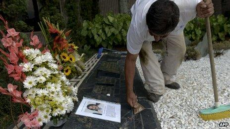 A man cleans the tomb of Colombian drug lord Pablo Escobar on 29 November, 2013 at Montesacro cemetery in Medellin