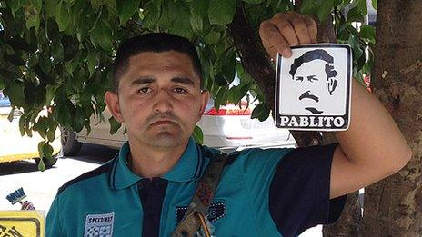 A street vendor holds up a sticker with an image of Pablo Escobar