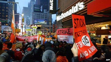 Demonstrators protest outside a McDonald's restaurant near New York's Times Square on 5 December 2013
