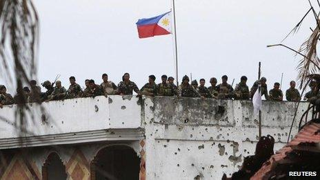 Soldiers stand next to the Philippine national flag on a mosque formerly occupied by Muslim rebels of Moro National Liberation Front (MNLF) in Zamboanga city, southern Philippines, 28 Sept