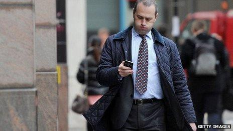 A man looking confused at his mobile phone