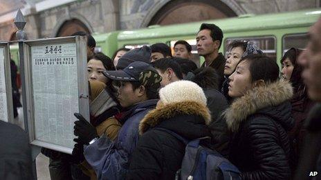 Metro commuters in Pyongyang read public newspaper