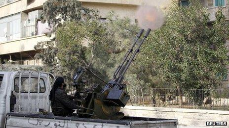 Syrian jihadist rebel from the al-Nusra Front fires an anti-aircraft weapon in Aleppo (18 December 2013)