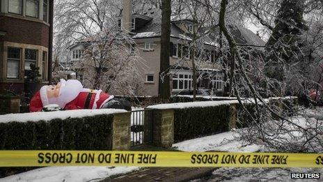 A giant inflatable Santa is knocked over behind a tree limb that has fallen over a power line following an ice storm