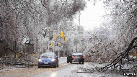 Vehicles drive around ice-covered tree branches that came down after freezing rain