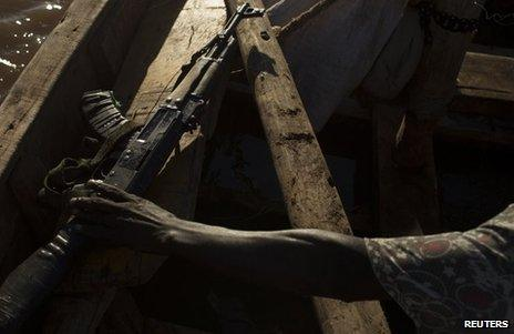 A man reaches for an AK47 assault rifle during a fishing expedition on Lake Turkana in north-western Kenya October 13