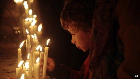 A boy lights a candle marking the events that launched 17 years of military rule in Santiago, Chile. September 2013
