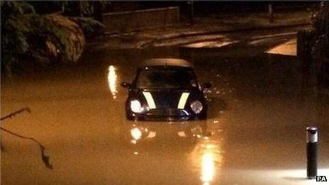 A Mini is caught in flooding in Mallards Way, Maidstone, Kent