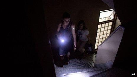 Using her cell phone as a flash light, a woman walks up the stairs to her sixth floor apartment in a building that has been without electricity for two weeks in Buenos Aires on 26 December, 2013