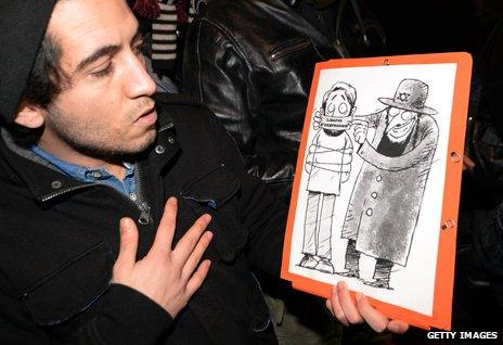 A Dieudonne supporter displays an anti-Jewish cartoon