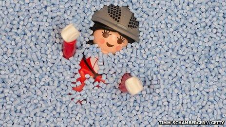 Plastic Playmobil toy character covered in plastic granules
