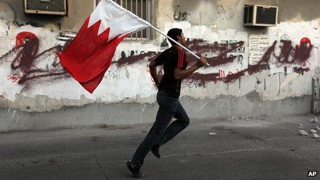 A Bahraini anti-government protester runs with a national flag during clashes with riot police firing tear gas in Sanabis, Bahrain, 18 October 2013