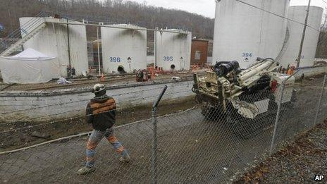 A worker moves a drilling machine around storage tanks at Freedom Industries storage facility in Charleston, West Virginia 13 January 2014