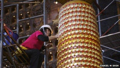 A roped climber removes Buddha statues from a tall column at the Fo Guang Shan temple in Kaohsiung