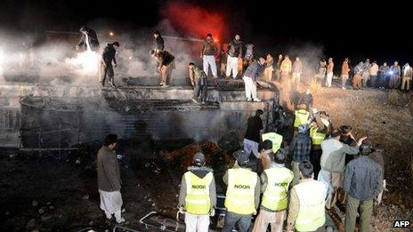 Pakistani rescuers and security personnel gather around a burnt passenger bus carrying Shia pilgrims at the site of a suicide bombing in Akhtarabad, on the outskirts of Quetta, the capital of Balochistan province on 1 January 2014