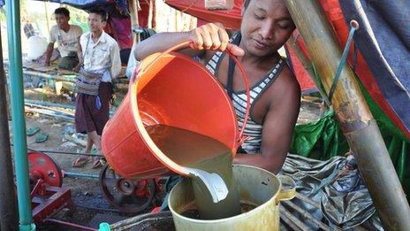 Oil worker pouring a bucket of oil