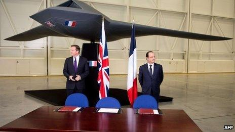 David Cameron and Francois Hollande stand beneath a model of an unmanned aircraft