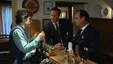 David Cameron and Francois Hollande speak to the landlord of The Swan Inn