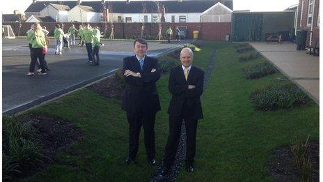 Two men stand in a large ditch next to a school playground