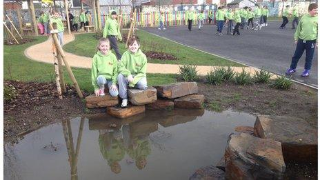 Two children sitting on rocks next to a pond next to a school playground