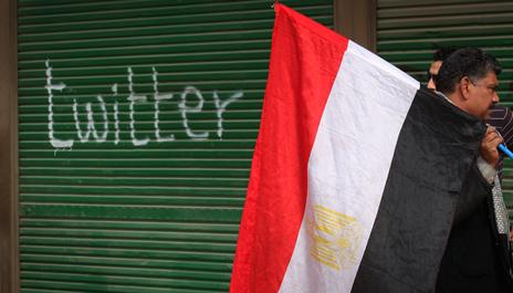 """Protester with Egyptian flag by """"twitter"""" graffiti, Tahrir Square 2011"""